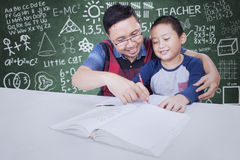 Teacher guide a little boy to learn. Portrait of male teacher guide a little boy to learn and write on the book, shot with doodles background on chalkboard Royalty Free Stock Photos