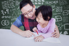 Teacher guide a little girl to learn. Portrait of teacher guide a little girl to learn and write on the book, shot with doodles background on chalkboard Royalty Free Stock Photos