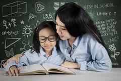 Teacher guides her student to read a book Stock Photos