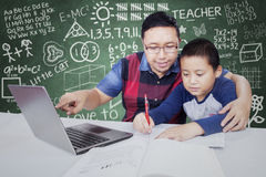 Teacher guides his male student to study. Young teacher pointing at laptop in the classroom while guiding his male student to study Stock Images