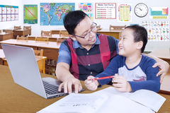 Teacher guiding male student in the classroom Royalty Free Stock Photos
