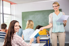 Teacher handing paper to student in class Royalty Free Stock Photography