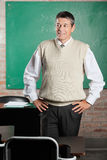 Teacher With Hands On Hips Looking Away In. Mature male teacher with hands on hips looking away while standing in classroom Royalty Free Stock Photography