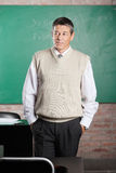 Teacher With Hands In Pockets Looking Away In. Thoughtful male teacher with hands in pockets looking away in classroom Royalty Free Stock Photo