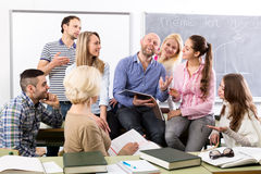 Teacher and happy adult students. Teacher and happy students during break in classroom Royalty Free Stock Photo