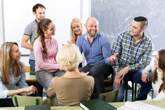 Teacher and happy adult students. Male teacher and adult students during break in classroom Stock Photos