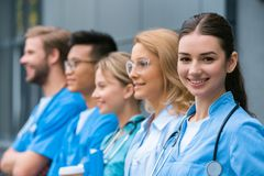 Teacher and happy multicultural students standing in row. Near medical university royalty free stock image