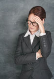 Teacher with headache. On the school blackboard background royalty free stock photos