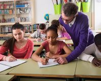 Teacher helping African-American pupil in classroom. Male teacher helping African-American pupil in classroom Royalty Free Stock Photos