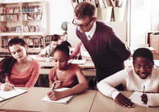Teacher helping African-American pupil in classroom. Teacher helping African-American pupil in multi-ethnic classroom Royalty Free Stock Photography