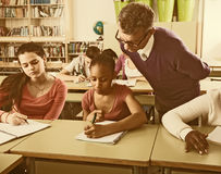 Teacher helping African-American pupil in classroom. Ordinary teacher helping African-American pupil in classroom Royalty Free Stock Photos