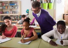 Teacher helping African-American pupil in classroom. Teacher helping African-American pupil in multi-ethnic classroom Royalty Free Stock Image