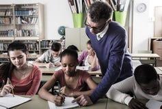 Teacher helping African-American pupil stock photos