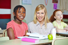 Teacher helping african girl Stock Images