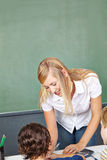 Teacher helping boy in elementary school Royalty Free Stock Photography