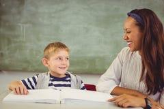 Teacher helping a boy with his homework in classroom Stock Photos