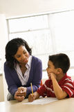 Teacher Helping Boy With Schoolwork Stock Photography