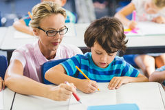Teacher helping a boy with studies in classroom Royalty Free Stock Photography