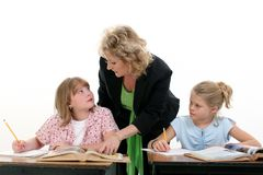 Teacher Helping Child in Classroom royalty free stock photography