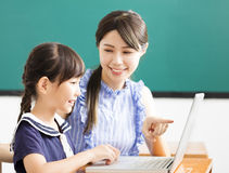 Teacher helping child with computer lesson Stock Photos