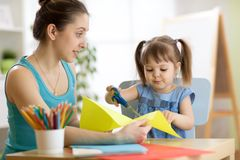 Teacher helping child to cut colored paper Stock Photo
