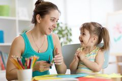 Teacher helping child to cut colored paper Royalty Free Stock Photos