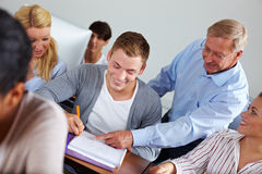 Teacher helping in class. Teacher helping some students in university class stock photos