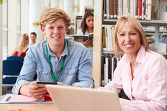 Teacher Helping College Student With Studies In Library Stock Images