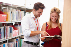 Teacher Helping College Student With Studies In Library Royalty Free Stock Photography