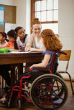 Teacher helping a disabled pupil Stock Photo