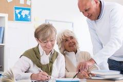 Teacher helping elder student Stock Images