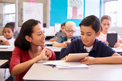 Teacher helping elementary school boy using tablet computer Royalty Free Stock Photo