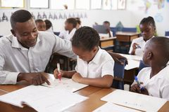 Teacher helping elementary school girl at her desk in class Royalty Free Stock Images