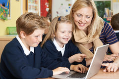 Teacher Helping Elementary School Pupils In Computer Class royalty free stock photography