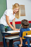 Teacher helping elementary school student Stock Photography