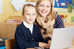 Teacher Helping Female Elementary School Pupil In Computer Class Stock Images