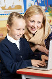 Teacher Helping Female Elementary School Pupil In Computer Class Royalty Free Stock Images