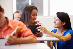 Teacher Helping Female High School Student In Classroom. Close Up Of Teacher Helping Female High School Student In Classroom Using Digital Tablet Royalty Free Stock Photography