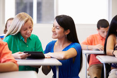 Teacher Helping Female High School Student In Classroom. Whilst Using Digital Tablet Royalty Free Stock Photography