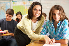 Teacher Helping Female Pupil Studying At Desk In Classroom Stock Photography