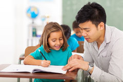 Teacher helping girl Stock Images