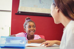 Teacher helping a girl with her homework in classroom Royalty Free Stock Images