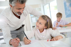 Teacher helping a girl pupil in class Royalty Free Stock Photography