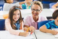 Teacher helping a girl with study's in classroom. Teacher helping a girl with studies in classroom at school Stock Photo