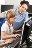 Teacher helping girl using computer in class. Sitting at the desk Stock Photo
