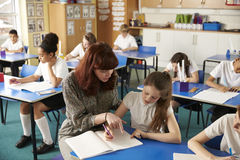 Teacher helping a girl with work at her desk, elevated view Royalty Free Stock Photo