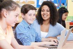Teacher Helping Group Of Elementary School Children In Computer Stock Photo