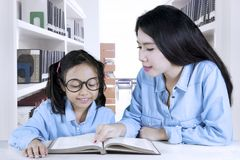 Teacher helping her student to reading a book. Picture of young teacher helping her student to reading a book while sitting in the library Stock Photography