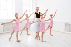Teacher helping her students during dance class stock photography