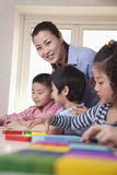Teacher Helping Her Students and Looking at Camera Royalty Free Stock Image